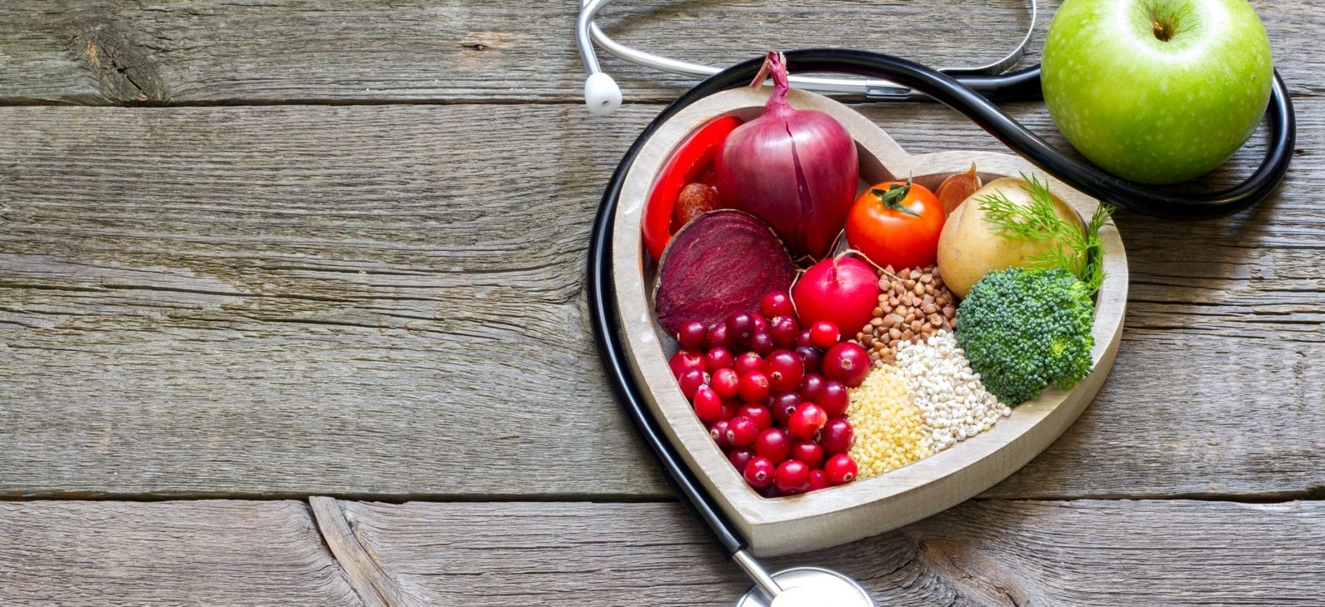Life to the Fullest: Picture of wood background with heart-shaped container filled with different colorful fruits and vegetables surrounded by a stethoscope