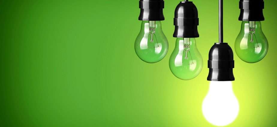 green background with 4 light bulbs hanging down, one of them is lit up