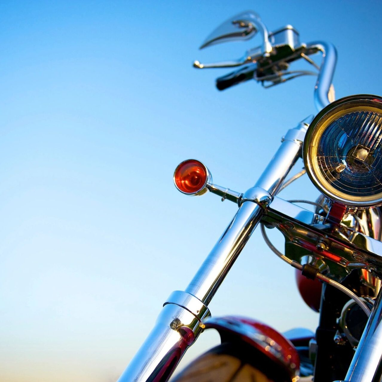 Close-up of front of motorcycle with blue sky background